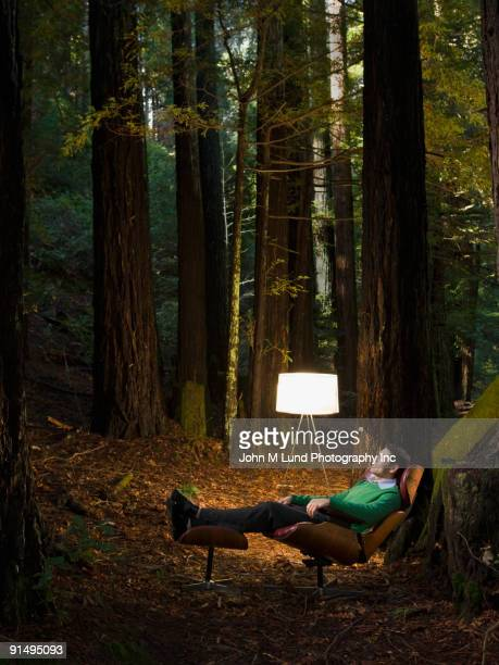 Mixed Race man relaxing in woods