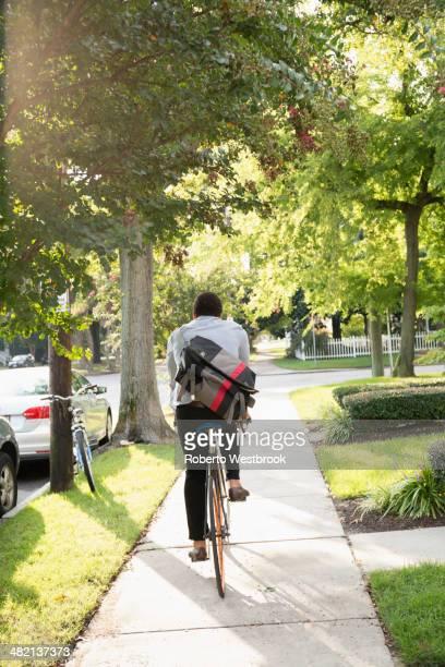 Mixed race man riding bicycle on suburban sidewalk