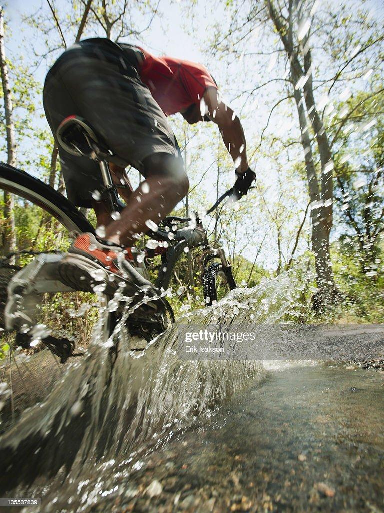 Mixed race man riding mountain bike through stream : Stock Photo