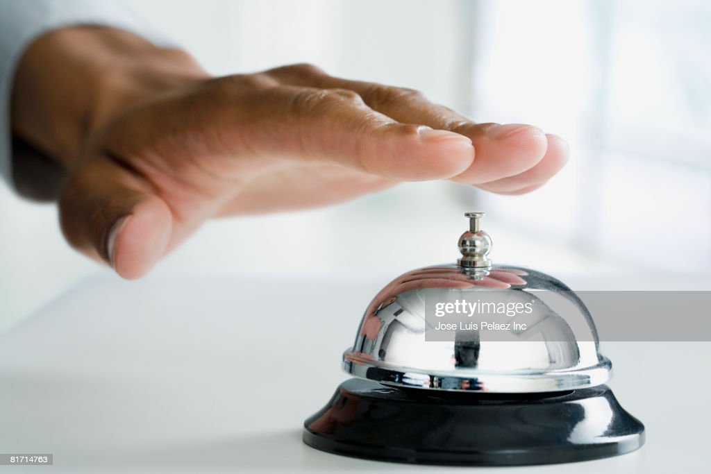 Mixed Race man ringing service bell : Stock Photo