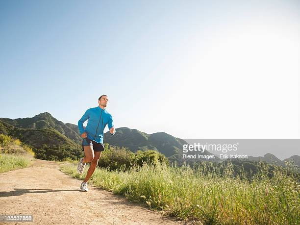 Mixed race man running on remote trail