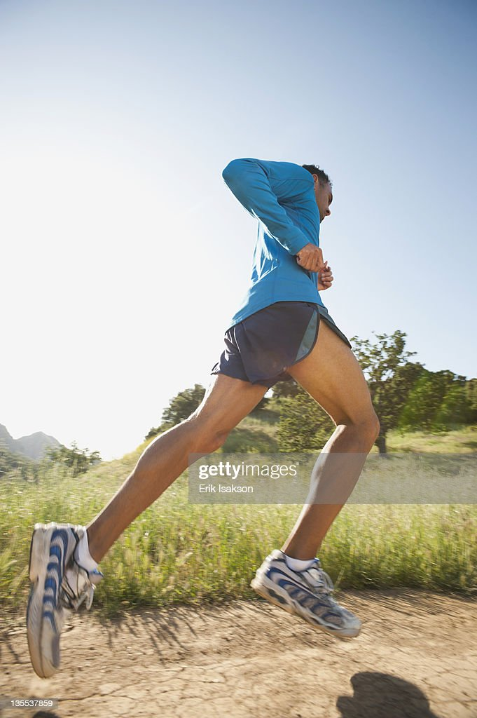 Mixed race man running on remote trail : Stock Photo