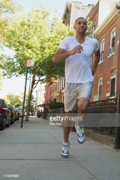 Mixed race man running on urban sidewalk