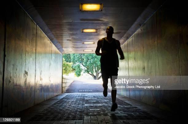 Mixed race man running through tunnel