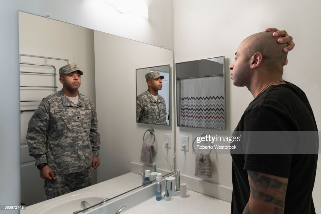 Mixed race man seeing soldier in mirror