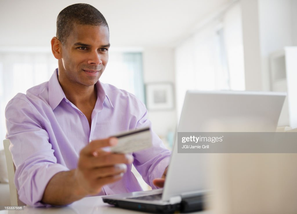 Mixed race man shopping online with credit card : Stock Photo