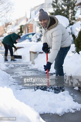 Mixed race man shoveling snow from sidewalk : Stock Photo