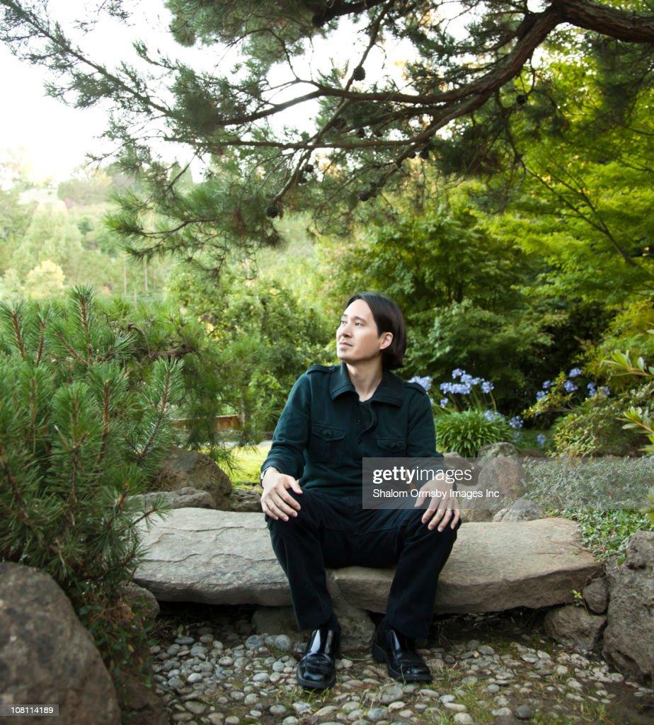 Mixed race man sitting in garden : Stock Photo