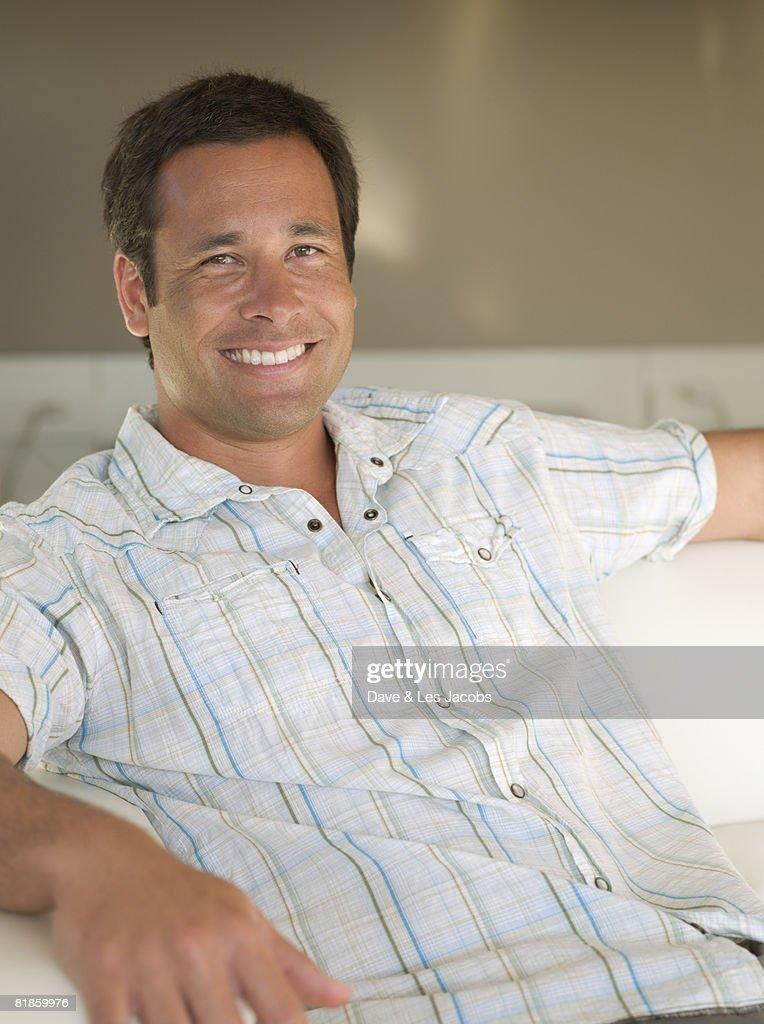 Mixed Race man sitting on sofa : Stock Photo