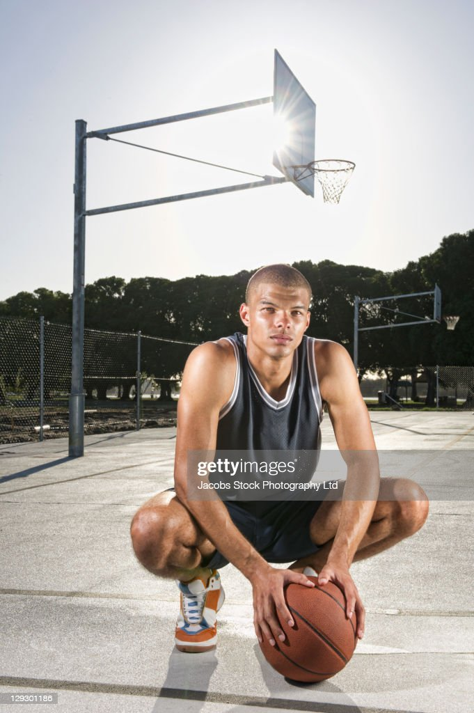 Mixed race man squatting with basketball : Stock Photo