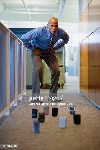 Mixed race man staring at cell phones on office floor