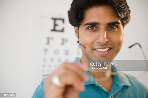 Mixed race man taking of eyeglasses