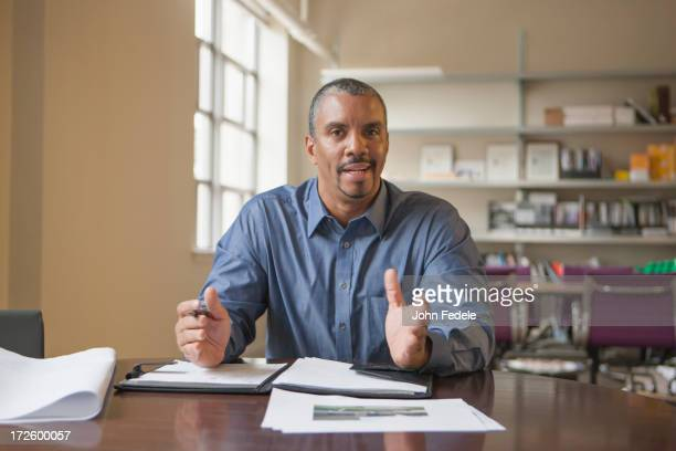 Mixed race man talking at desk