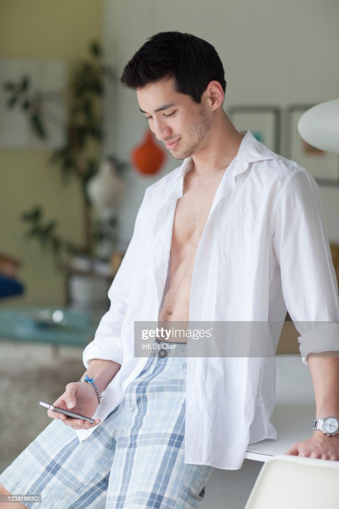 Mixed race man text messaging on cell phone : Stock Photo