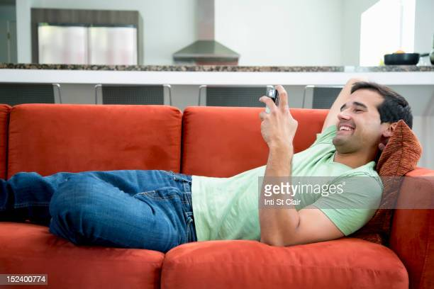 Mixed race man text messaging on cell phone