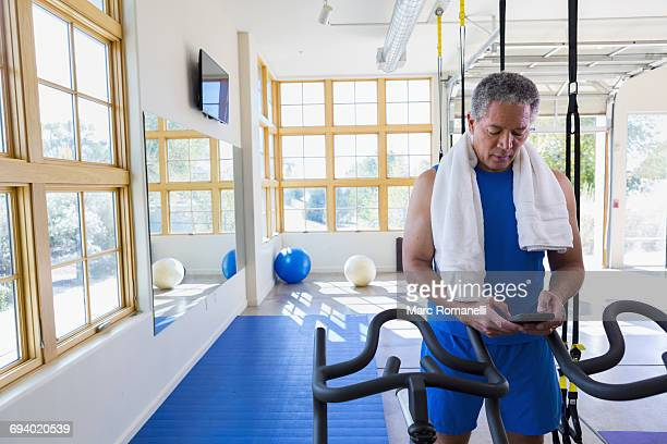 Mixed Race man texting on cell phone in gymnasium