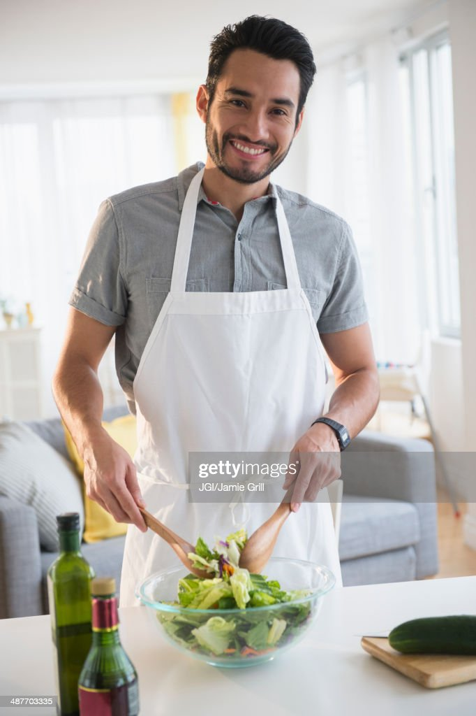 Mixed race man tossing salad at table