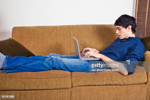 Mixed race man typing on laptop on sofa