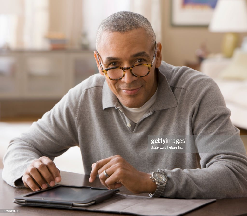 Mixed race man using digital tablet : Stock Photo
