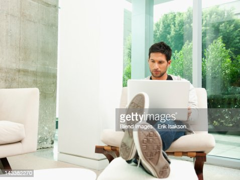 Mixed race man using laptop in living room
