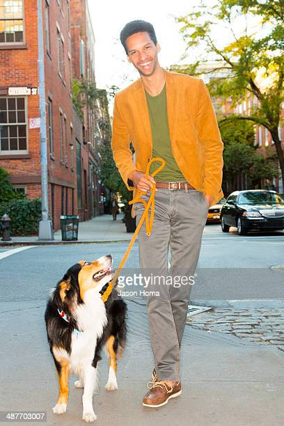 Mixed race man walking dog on city street