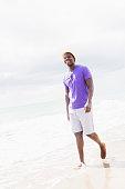 Mixed race man walking on beach