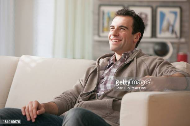 Mixed race man watching television