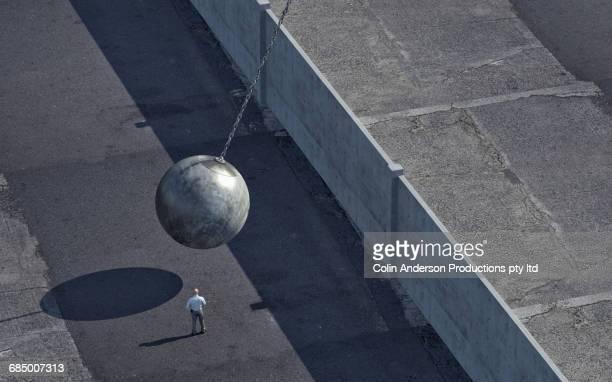 Mixed Race man watching wrecking ball swinging at wall