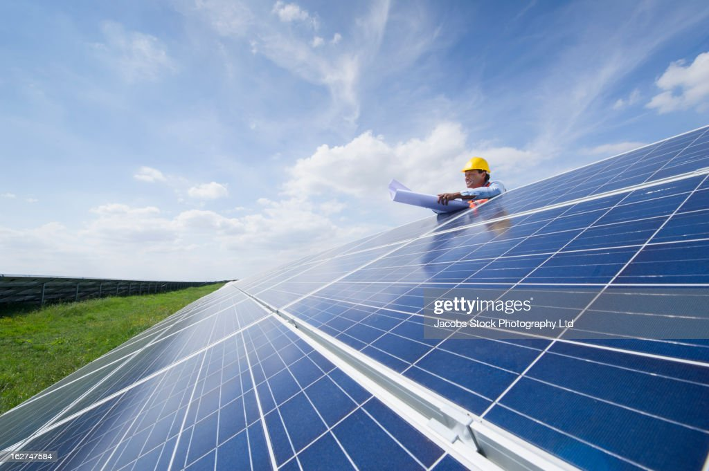 Mixed race man with blueprints checking solar panels