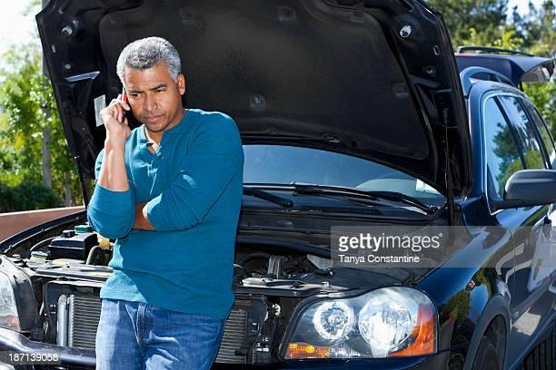 Mixed race man with broken down car