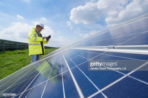 Mixed race man with digital tablet checking solar panels