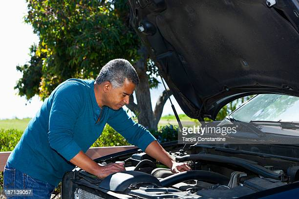 Mixed race man working on car engine