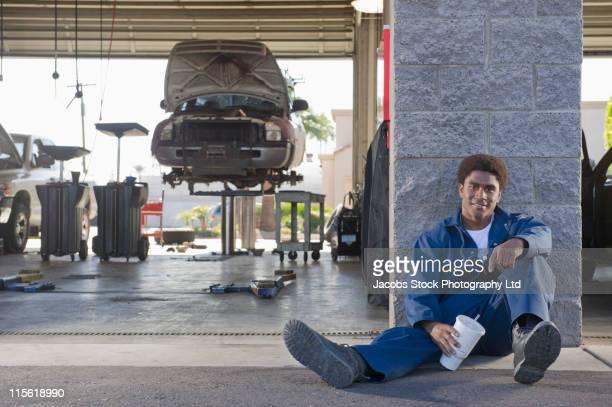 Mixed race mechanic taking a break in auto repair ship