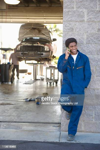 Mixed race mechanic talking on cell phone