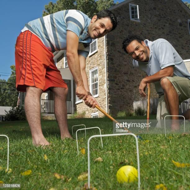 Mixed race men playing croquet