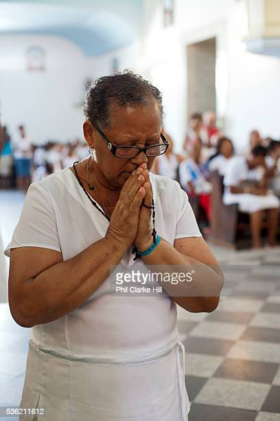 Mixed race middle aged Brazilian woman praying in Church at front of ceremony Often the lines between Candomble and Catholicism are blurred This is...