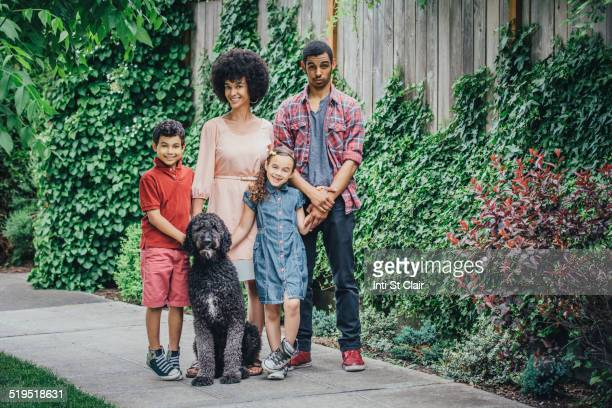Mixed race mother and children smiling with dog on suburban sidewalk
