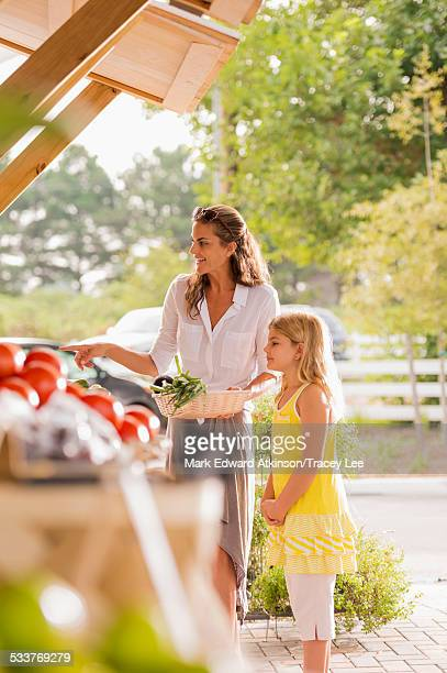 Mixed race mother and daughter browsing produce at farmers market