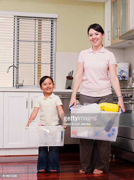 Mixed Race mother and daughter holding recycling bins