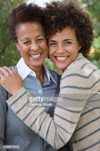 Mixed race mother and daughter hugging : Stock Photo
