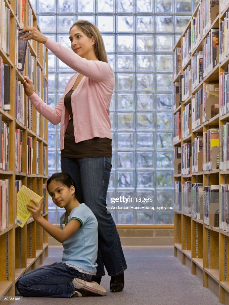 Mixed Race mother and daughter looking at library books
