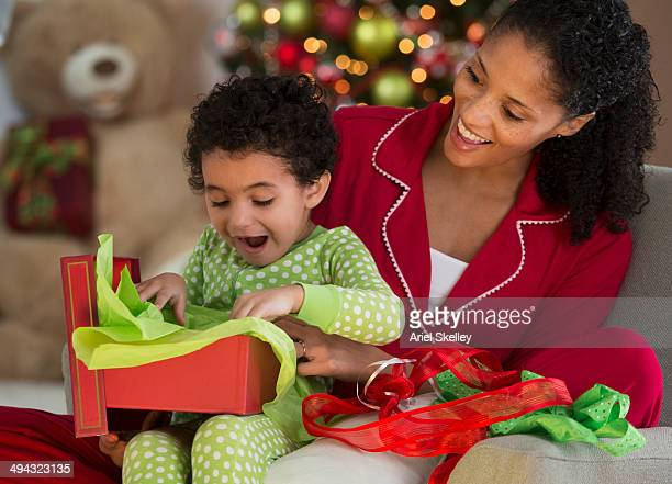 Mixed race mother and daughter opening Christmas present