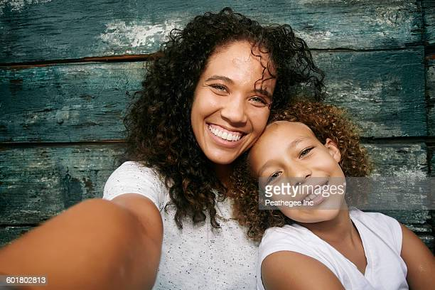 Mixed race mother and daughter taking selfie