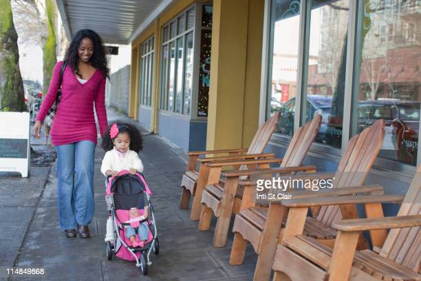 Mixed race mother and daughter walking on sidewalk
