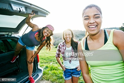 Mixed Race mother and daughters at hatch of car laughing