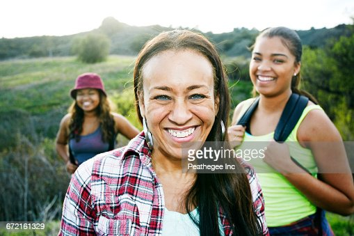 Mixed Race mother and daughters backpacking in field