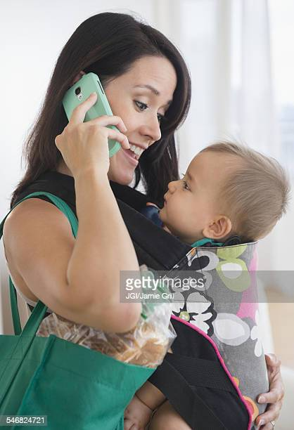 Mixed race mother carrying baby and talking on cell phone