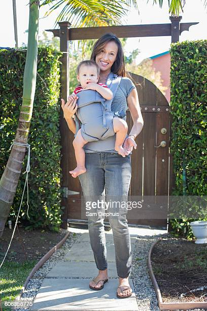 Mixed race mother carrying baby in sling