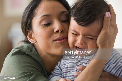 Mixed race mother comforting baby boy
