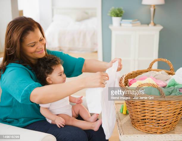 Mixed race mother folding laundry and holding baby